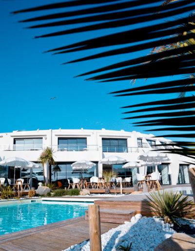 Moment de détente à l'abri du soleil au bord de la piscine chauffée, hotel piscine la grande motte, Hôtel La Plage.