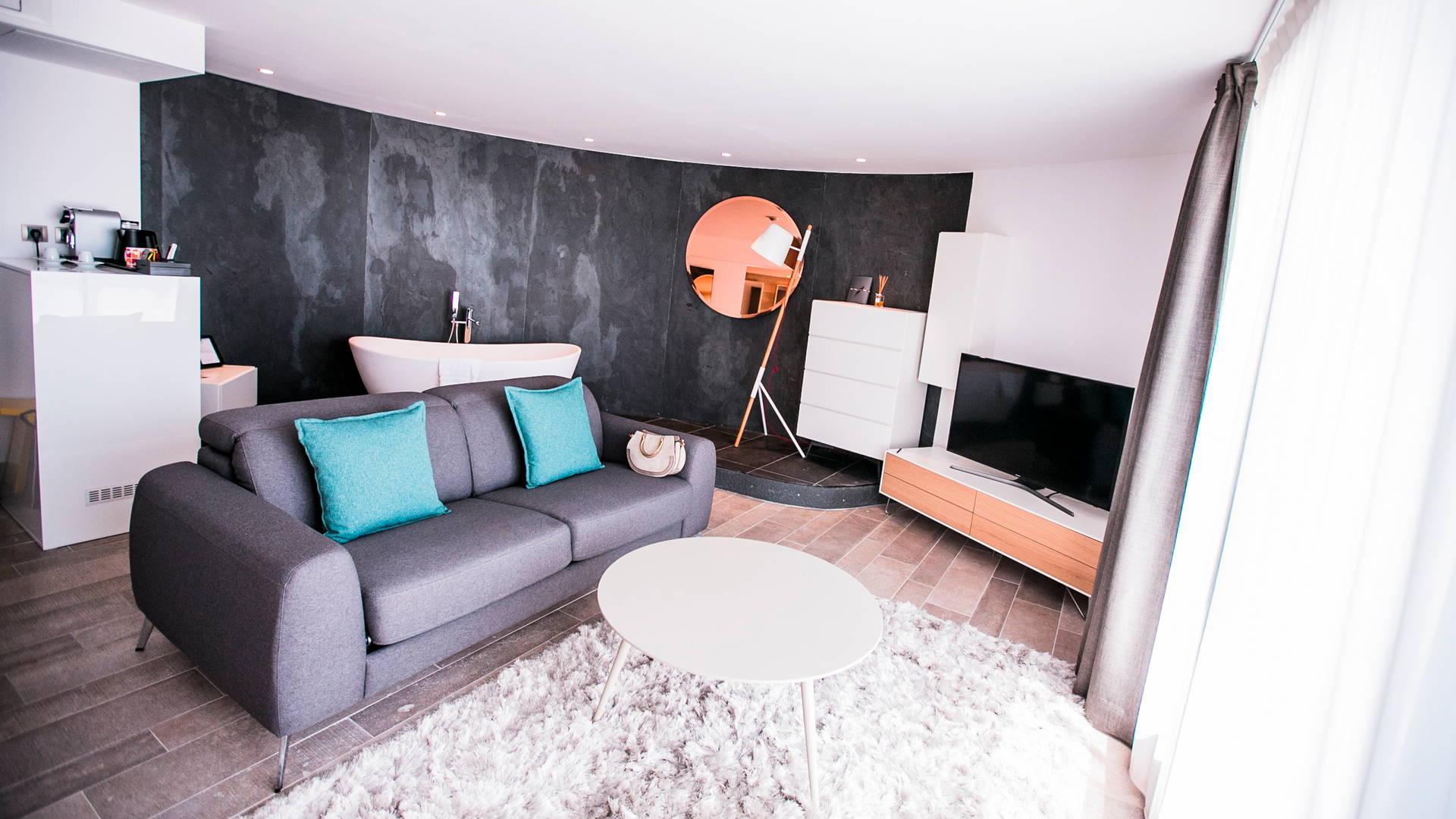 Suite La Plage avec canapé, télévision et baignoire dans le salon, Hôtel bord de mer méditerranée, Hôtel La Plage.