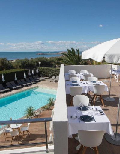 Tables de restaurant en extérieur avec sur l'horizon et la mer, hôtel piscine la grande motte, Hôtel La Plage.