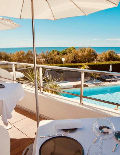 Table de restaurant sous les parasols avec vue sur la mer et la piscine de l'hôtel, hôtel piscine la grande motte, Hôtel La Plage.