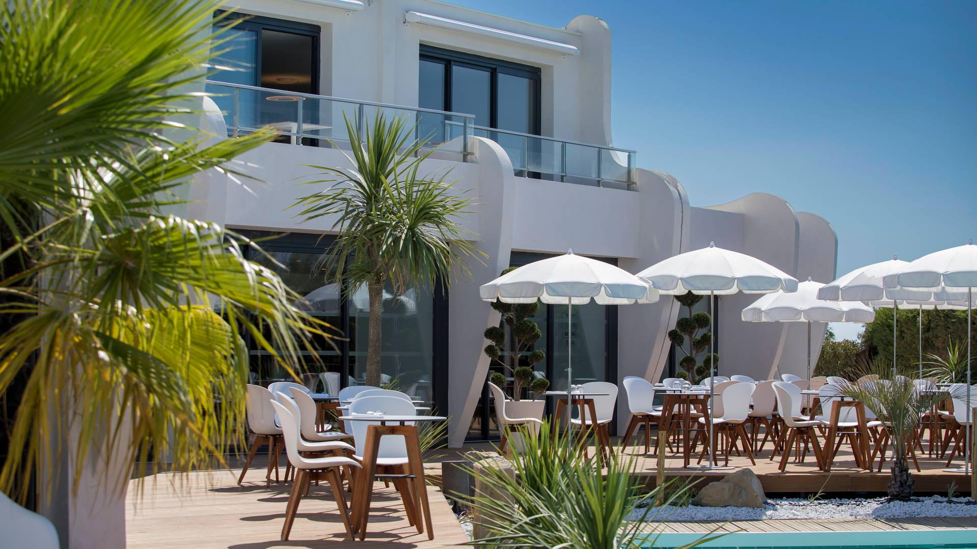 Façade de l'hôtel depuis la piscine extérieure avec terrasse extérieur du restaurant avec des parasols, hôtel la grande motte bord de mer, Hôtel La Plage.