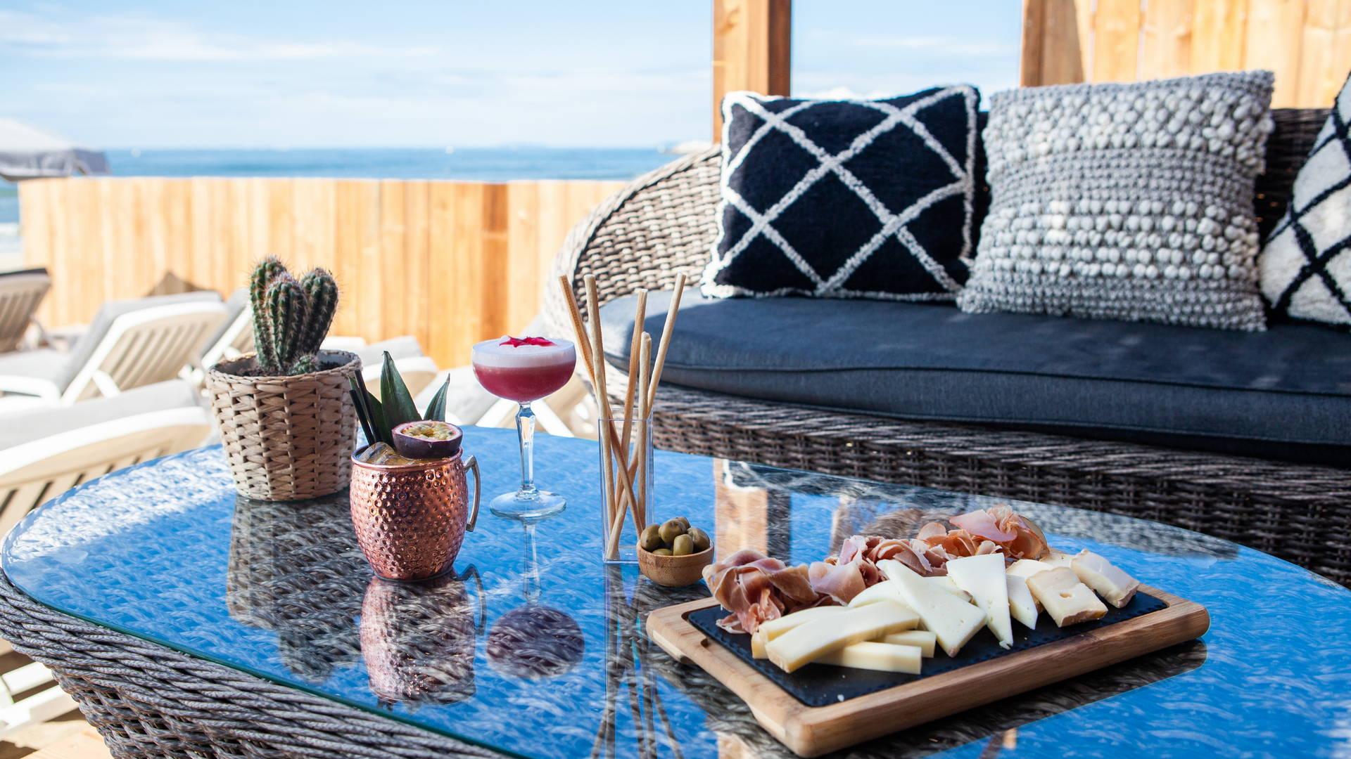 Espace avec canapé et planche de charcuterie et fromage accompagné d'un cocktail au bord de l'eau, plage privée la grande motte, Hôtel La Plage.