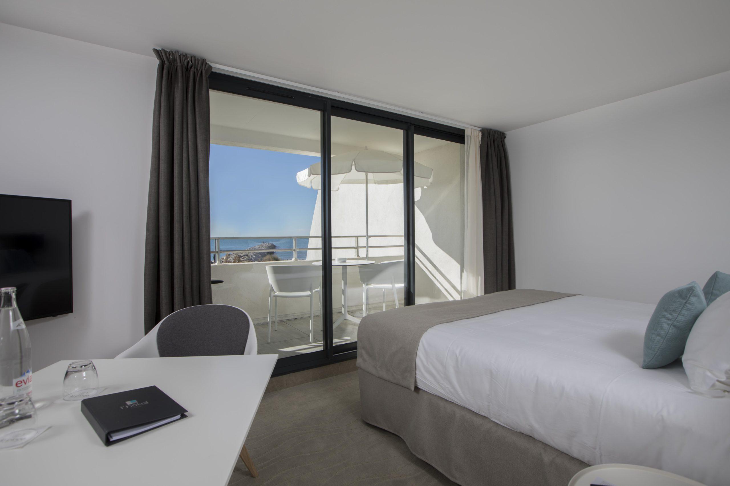 Chambre avec lit simple et balcon avec table et chaises, hôtel vue sur mer, Hôtel La Plage.