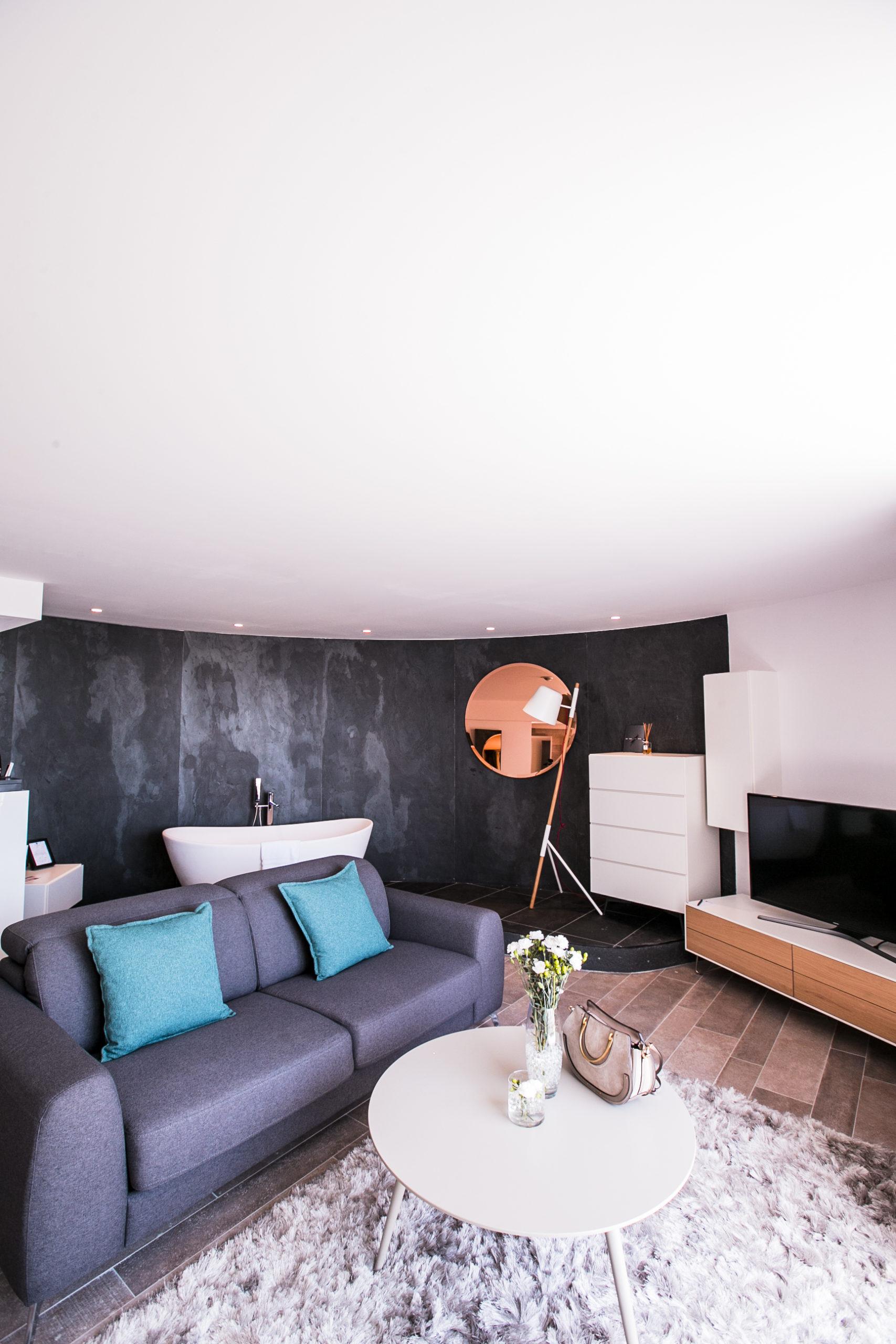 Chambre spacieuse à la décoration moderne avec canapé, télévision et baignoire, hotel bord de mer méditerarranée, Hôtel La Plage.